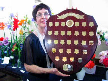 President Lyn Dahl holding the Joy Bowley Perpetual Trophy for Supreme Champion Dairy Goat